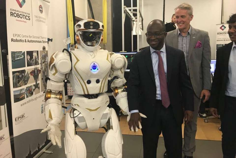 MP Sam Gyimah holds hands with humanoid robot, Valkyrie.